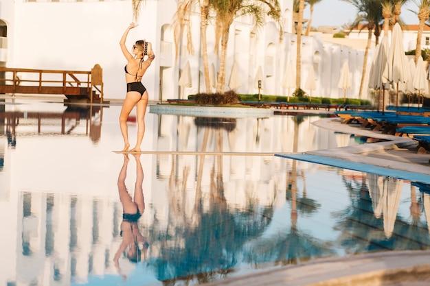 Junge sexy frau, die modischen schwarzen badeanzug, bikini, nahe großen schönen pool, resort trägt. hotel. frohe sommerzeit, urlaub, urlaub, spa