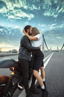 Junge sexy frau, die niedlichen mann in der stilvollen schwarzen lederjacke umarmt, sitzt auf sportmotorrad auf der brücke in der stadt auf sonnenuntergang und küsst.