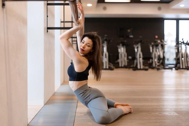 Junge sexy frau, die übungen in der turnhalle ausdehnend tut