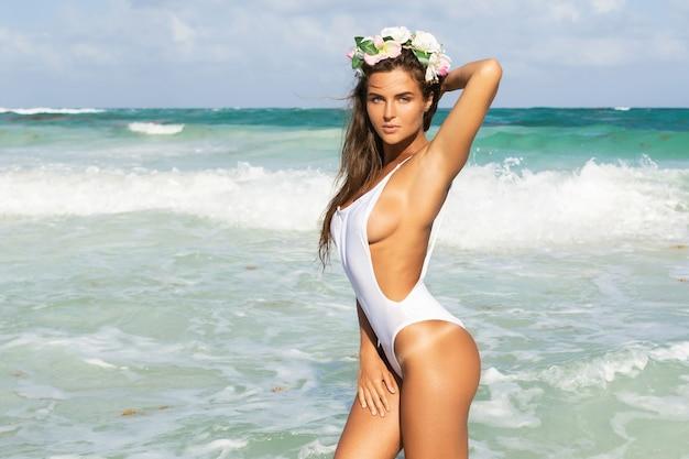 Junge sexy frau, die weißen badeanzug trägt, posiert am strand