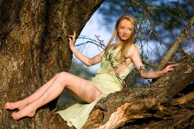 Junge sexy frau im grünen kleid, das auf baumstamm über wasser am sommertag mit grüner natur am hintergrund sitzt