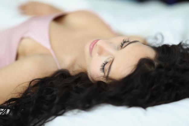 Junge sexy frau im rosa peignoir, die im bett liegt. gesundes schlafkonzept