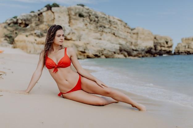 Junge sexy frau im roten bikini, der am tropischen strand liegt