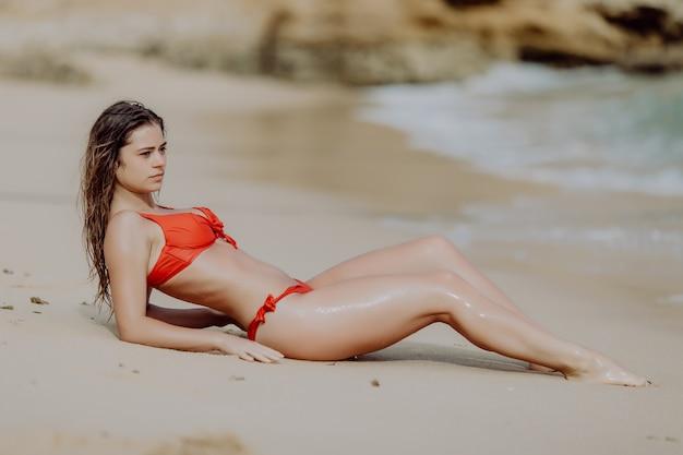 Junge sexy frau im roten bikini, der auf dem sand die ozeanküste liegt