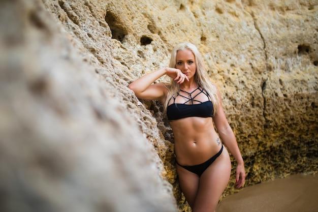 Junge sexy frau im schwarzen bikini, der auf einem sandfelsen nahe dem meer aufwirft