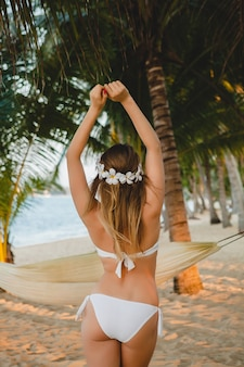 Junge sexy frau im weißen bikini-badeanzug, der auf tropischem strand, palmen, hawaii, blumen im haar, sinnlicher, schlanker körper, sonnig, blick von hinten aufgibt, urlaub genießt, auf insel reist