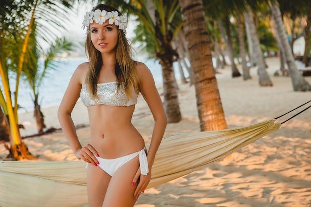 Junge sexy frau im weißen bikini-badeanzug, der auf tropischem strand, palmen, hawaii, blumen im haar, sinnlicher, schlanker körper, sonnig, urlaub genießt, auf insel reisend aufwirft