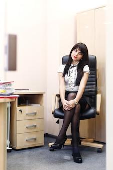 Junge sexy frau in den schwarzen strümpfen, die auf arbeitsplatz im büro sitzen