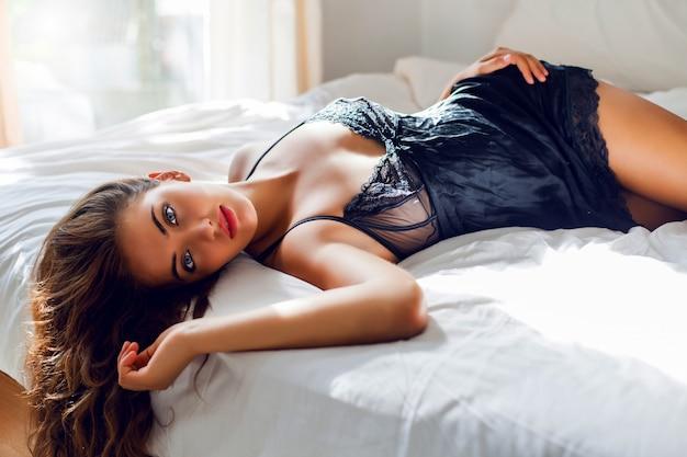 Junge sexy frau in der schwarzen wäsche, die im bett aufwirft