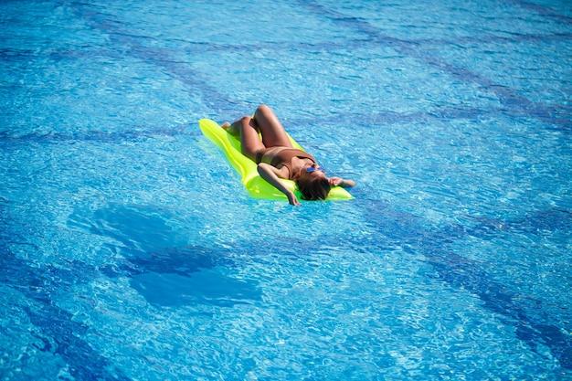 Junge sexy frau in einem badeanzug schwimmt im pool auf einer aufblasbaren matratze. mädchen mit sonnenbrille in einem blauen pool im urlaub