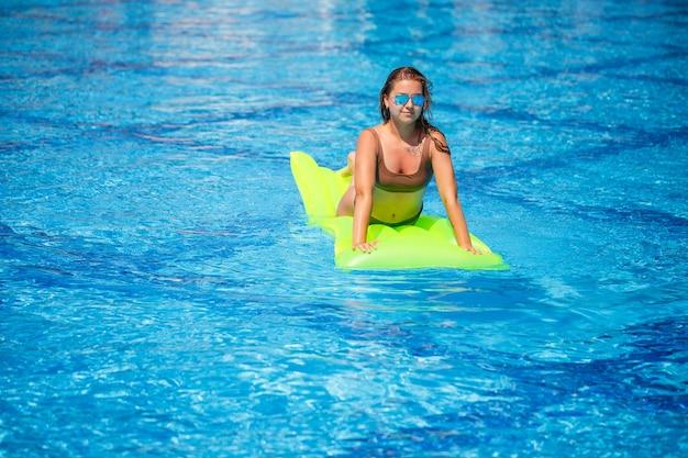 Junge sexy frau in einem badeanzug schwimmt im pool auf einer aufblasbaren matratze. mädchen mit sonnenbrille mit einem lächeln auf den gesichtern in einem blauen pool im urlaub