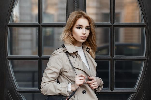 Junge sexy frau mit schönen augen in einem hellen frühlingsmantel mit einer modischen schwarzen tasche in einem weißen t-shirt nahe der vintage braunen spiegeltür. modisches europäisches modernes mädchen.