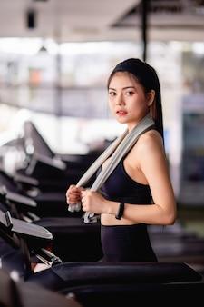 Junge sexy frau mit sportbekleidung, schweißfestem stoff und smartwatch, die auf dem laufband aufwärmt, bevor sie zum training im modernen fitnessstudio läuft, kopierraum