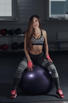 Junge sexy frau sitzt auf fitnessball in der turnhalle und schaut in die kamera.