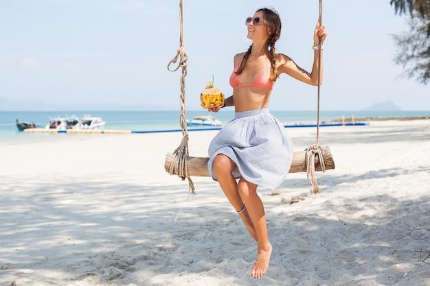 Junge sexy frau sitzt auf schaukel am tropischen strand, sommerferien, modestil, rock, bikinioberteil, trinkenden kokosnusscocktail, lächelnd, entspannend