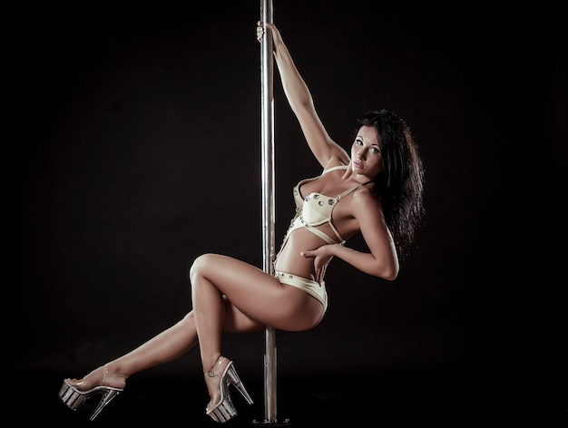 Junge sexy frau übt pole dance vor einem schwarzen hintergrund aus