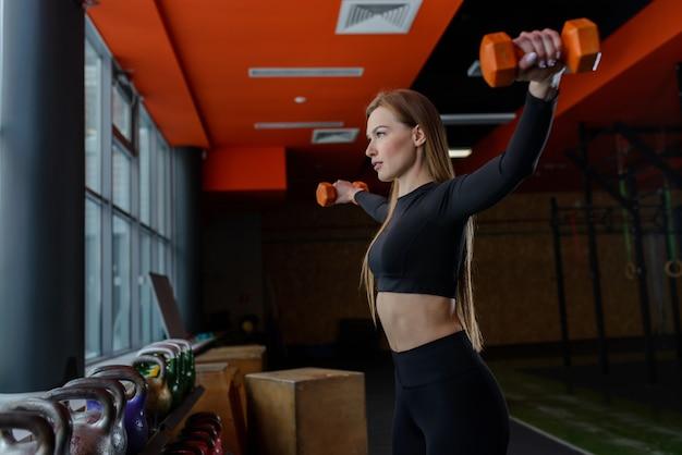 Junge sexy frau während des fitness-trainings im fitnessstudio