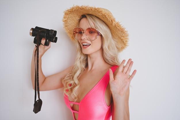 Junge sexy lächelnde glückliche blondine in einem rosa badeanzug, einem strohhut, sonnenbrille, aufgeregt, produkt zu präsentieren. frau auf einem weißen hintergrund mit palmengrünen blättern.