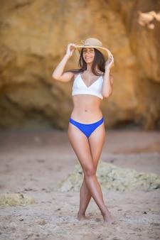 Junge sexy lateinische frau mit perfektem körper im bikini auf dem felsenstrandhintergrund