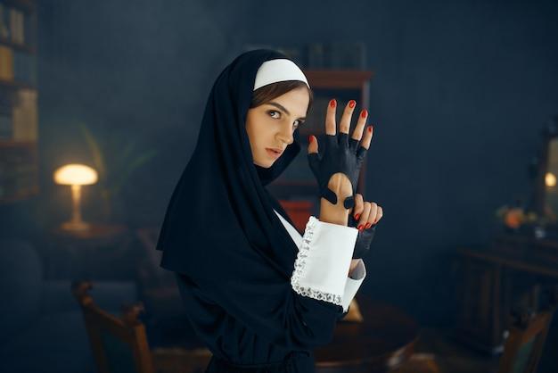 Junge sexy nonne in einer soutane zieht einen handschuh an, bösartige wünsche. korrupte schwester im kloster, religion und glaube, sündige religiöse menschen, attraktive sünderin