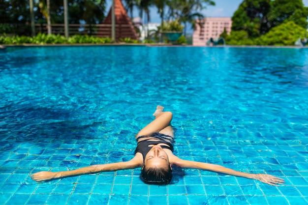 Junge sexy schlanke frau, die im tropischen schwimmbad mit kristallblauem wasser im heißen sommertag entspannt