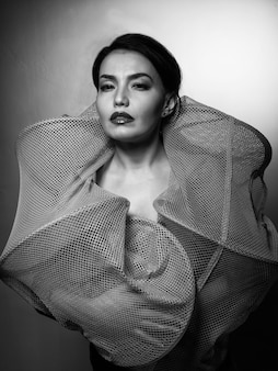 Junge sexy schlanke gebräunte frau in einem fischerkäfig, der gegen grauen raum aufwirft. schwarzweiss-modeporträt des schönen mädchens mit brünettem haar.