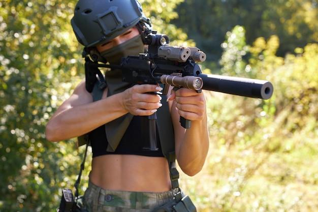 Junge sexy schlanke kaukasische soldatin, die mit gewehrmaschinengewehr im wilden wald schießt
