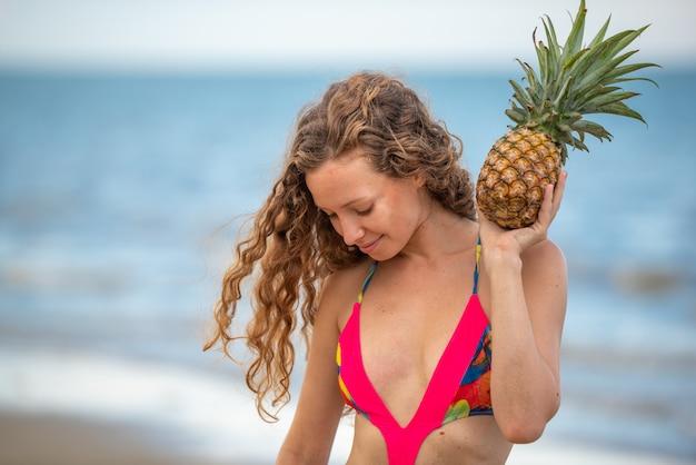 Junge sexy tropische frau, die ananas auf dem strand hält.