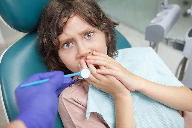 Junge sieht verängstigt aus, sitzt während der zahnärztlichen untersuchung im zahnarztstuhl und bedeckt seinen mund mit den händen