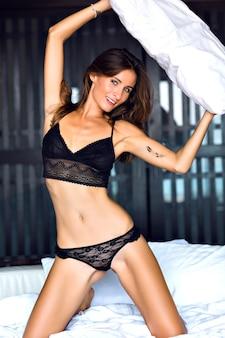 Junge sinnliche brünette frau, die mit kissen spielt, spaß am morgen hat und atemberaubende sexy schwarze dessous im boudoir-stil trägt