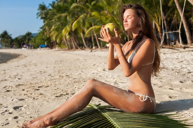 Junge sinnliche frau in der weißen bikini-badebekleidung, die kokosnuss hält, lächelnd, sonnenbad auf tropischem strand.