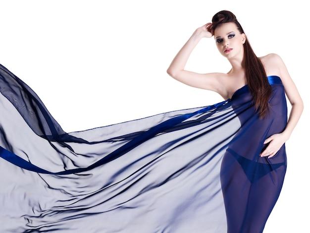 Junge sinnlichkeitsglamourfrau im dunkelblauen chiffon auf weiß