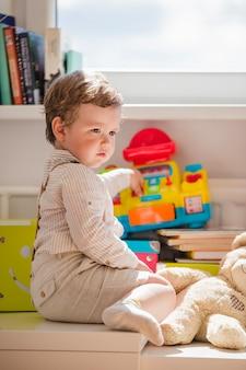 Junge sitzt am fenster spielen mit spielzeug