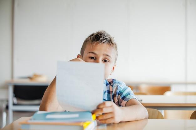 Junge sitzt am schreibtisch halten blatt
