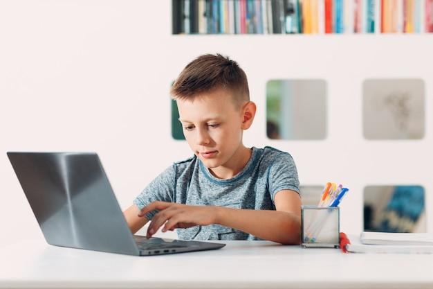 Junge sitzt am tisch mit laptop und bereitet sich auf das schulkonzept für die online-bildung vor