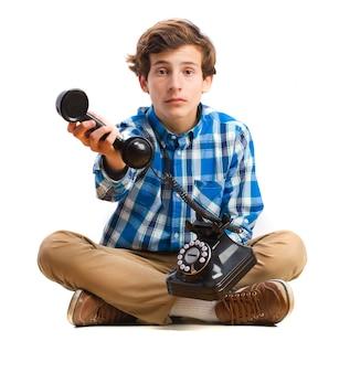 Junge sitzt auf dem boden und hält einen weinlesetelefon