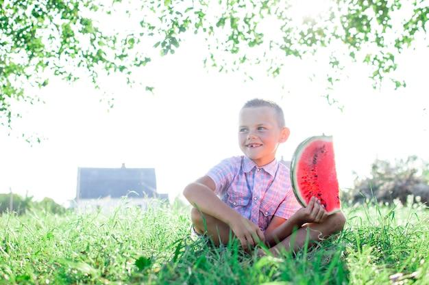Junge sitzt auf dem grünen gras im dorf und hält ein großes stück wassermelone, ein kleiner schüler isst eine wassermelone an einem sonnigen sommertag, kopienraum