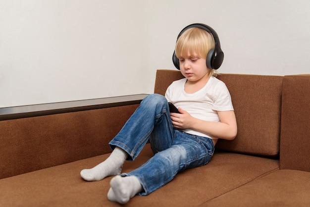 Junge sitzt auf der couch und schaut zum smartphone. probleme des modernen lebens kinder.
