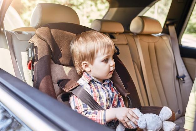 Junge sitzt in einem auto im sicherheitsstuhl familienausflug