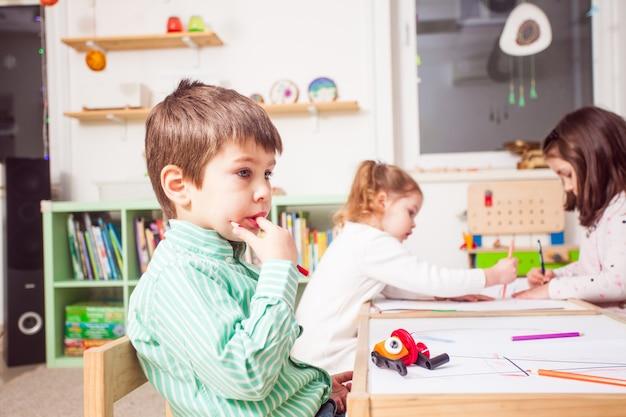 Junge sitzt und überlegt, was er im kindergarten malen soll