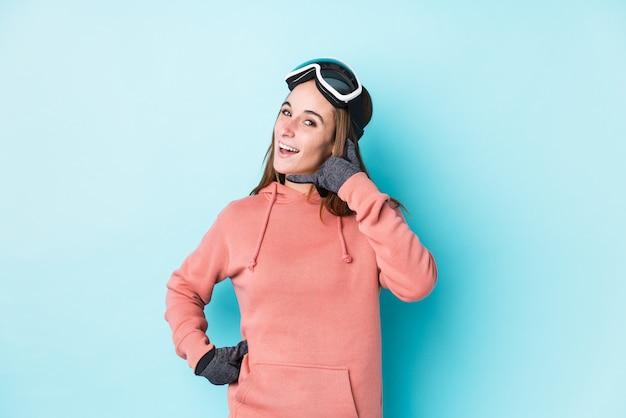 Junge skifahrerfrau, die eine handyanrufgeste mit den fingern zeigt