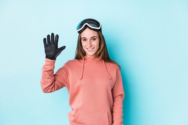 Junge skifahrerin isolierte lächelnd fröhlich und zeigte nummer fünf mit den fingern.