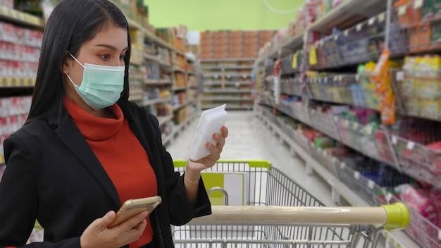 Junge smarte asiatische geschäftsfrau mit gesichtsmaske, die lebensmittel aus dem regal im supermarkt-kaufhaus oder einkaufszentrum kauft, neue normale coronavirus-krise oder covid19-ausbruch.