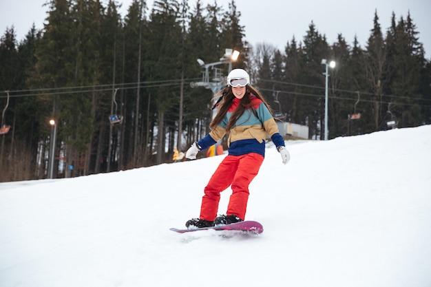 Junge snowboarderin auf der piste frostigen wintertag