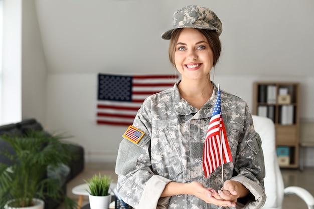 Junge soldatin mit usa-flagge im hauptquartier Premium Fotos