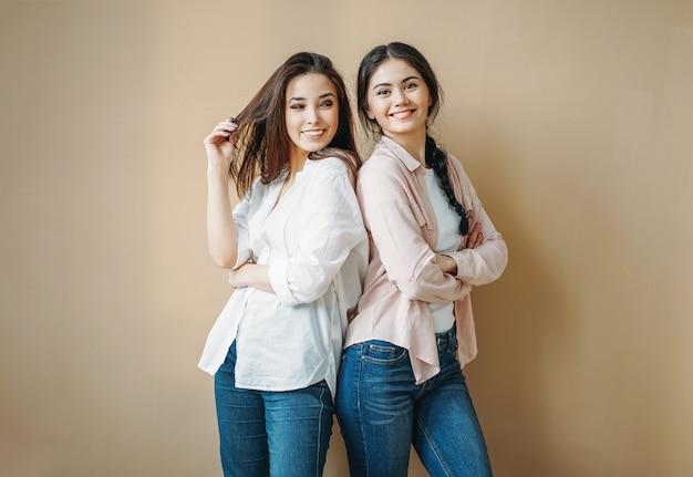 Junge sorglose brünette lächelnde freundinnen schwestern in freizeithemden und jeans lokalisiert auf beigem hintergrund