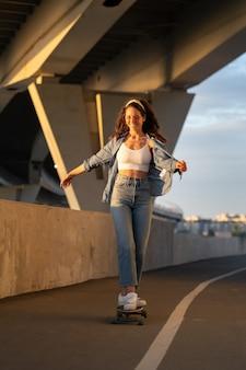 Junge sorglose frau genießt es, bei sonnenuntergang skateboard zu fahren, glückliches mädchen in trendiger streetstyle-kleidung