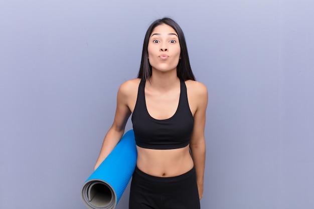 Junge späte frau mit einer yogamatte auf betonwand