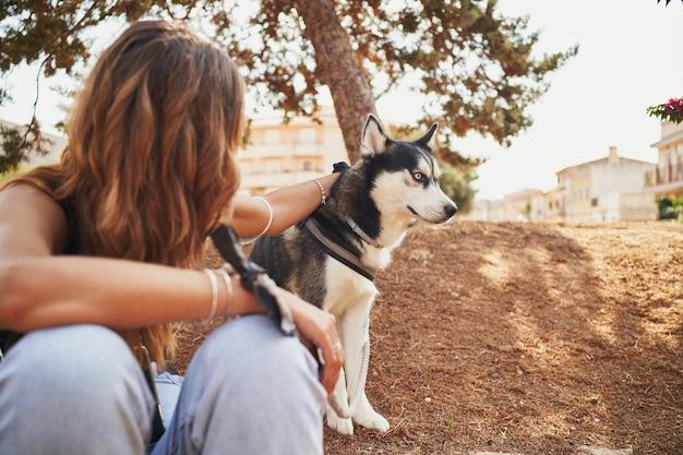 Junge spanierin sitzt mit ihrem siberian husky im park