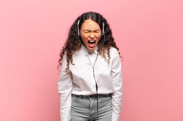Junge spanische frau, die aggressiv schreit, sehr wütend, frustriert, empört oder genervt aussieht und nein schreit. telemarketer-konzept